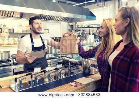 Waiter Serving Takeaway Food To Customers At Counter In Small Family Eatery Restaurant - Trendy Fast