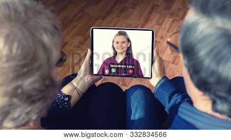 Senior Couple At Home Holding Digital Tablet During Video Call With Family Doctor - Virtual Live Con