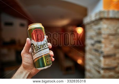 BUDAPEST, HUNGARY - JANUARY 29, 2018: Holding a can of Pilsner Urquell, popular Czech beer brewed in Plzen