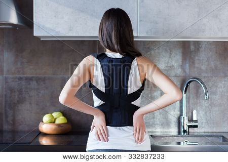 Brunette Girl Is Standing In Kitchen And Holding Hand On Back. Young Woman Dressed Orthopedic Bandag