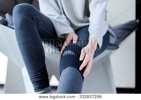 Closeup Female Leg In Grey Leggings Dressed In Knee Brace To Help Promote Recovery Of Bones, Muscles