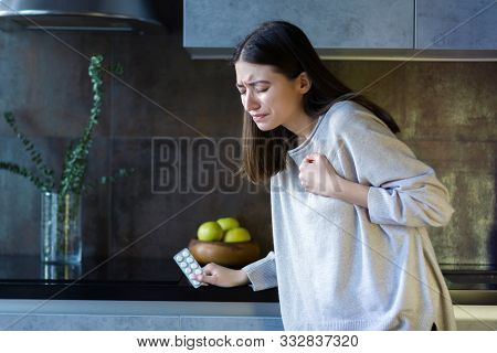 Young Woman In Grey Clothes Is Holding Hand On Breast And Going To Take Pills. Brunette Girl Is Feel