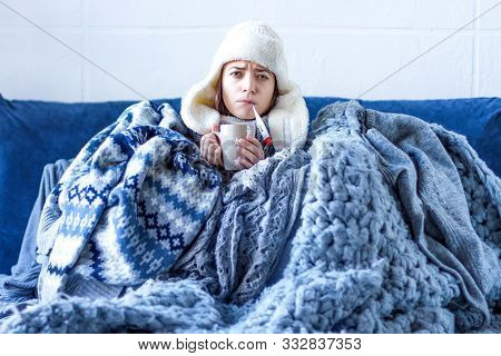 Sick Exhausted Girl In White Warm Hat Wrapped Herself In Scarves And Blankets Is Sitting In Bed. You