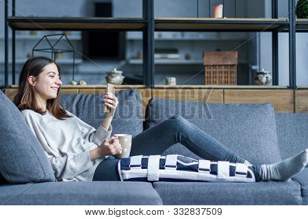 Smiling Brunette Girl With Broken Leg Is Sitting On Couch Sofa, Resting And Drinking Tea At Home. In