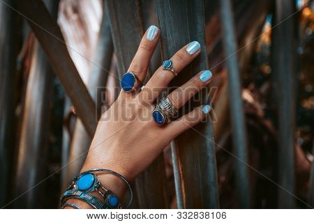 Close Up Of Woman Hand With Gemstone Rings On Tropical Background