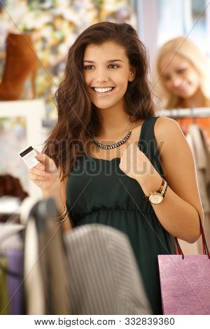 Attractive female paying by credit card at clothes store, smiling happy.