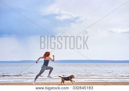 A Red-haired Middle-aged Woman In Sportswear Runs Along The Sandy Shore Of A Large River With Her Pu