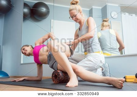 Woman stretching and relaxing in physical therapy exercise on fascia roll