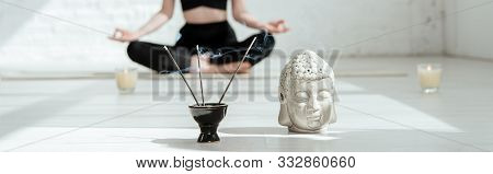 poster of cropped view of woman sitting in half lotus pose near buddha head sculpture, aromatic sticks and candles, panoramic shot