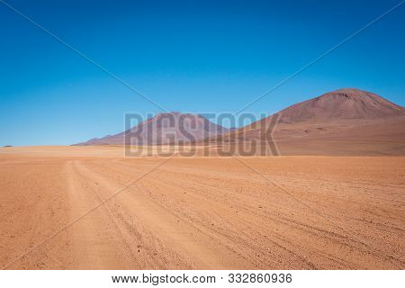 Dirt Tracks Continue Through The Orange Soil Of The Siloli Desert Travelling Past Countless Volcanoe