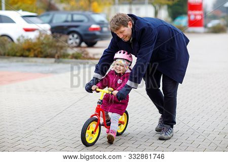 Cute Little Toddler Girl In Safety Helmet Riding On Run Balance Bike. Middle-aged Father Teaching Ha