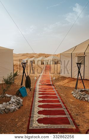Beautiful Desert Camp And Carpet Forming A Corridor With Tents In The Background.