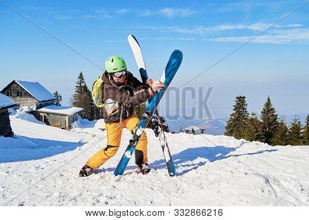Clumsy Funny Skier Holding His Skis Wrong. Location: Poiana Brasov Ski Resort, Romania.