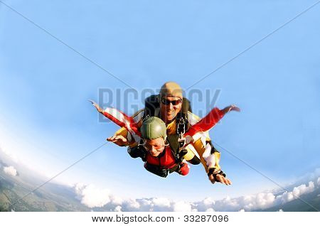 Porträtt av två tandem fallskärmshoppare i aktion fallskärmshoppning genom luften.