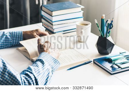 Man Reading Book On Modern Stylish Work Place With Office Supplies, Glasses, Notebooks And Books, De