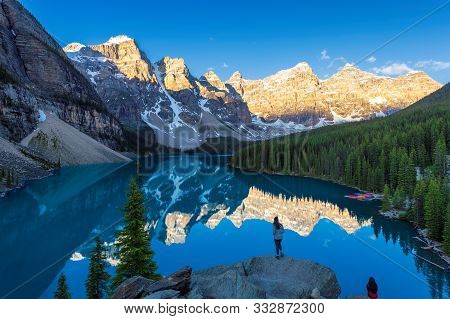 Beautiful Sunrise Under Turquoise Waters Of The Moraine Lake With Snow-covered Peaks In Banff Nation