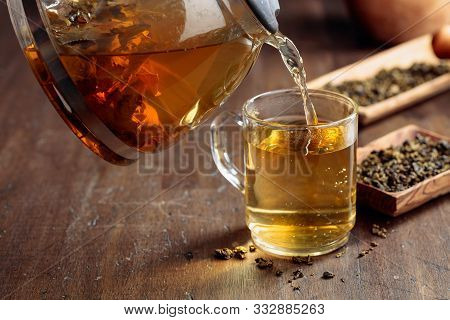 Fresh Green Tea Is Poured From A Teapot Into A Mug. Hot Green Tea In Glass Mug On A Wooden Table.