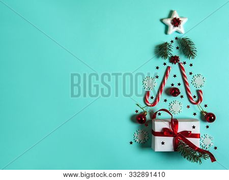 Christmas Composition. Christmas Tree Is Made Of White Snowflakes And Fir Branches, Caramel Canes, G