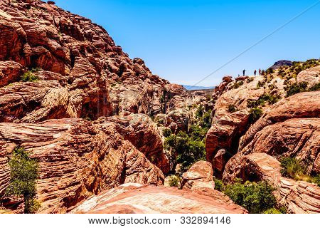 Tourists Standing On The Red Sandstone Cliffs At The Trail Head Of The Calico Hiking Trail In Red Ro