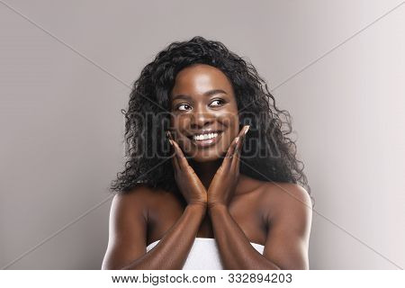 Rejuvenation Concept. Beautiful African American Woman Touching Her Perfect Skin On Cheeks And Looki