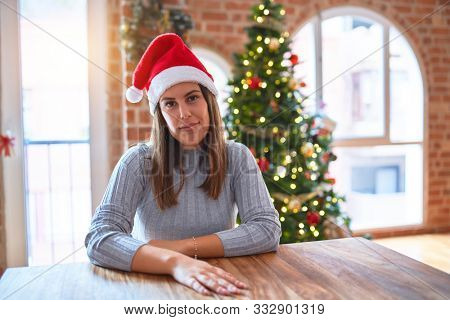 Young beautiful woman wearing santa claus hat at the table at home around christmas decoration with serious expression on face. Simple and natural looking at the camera.