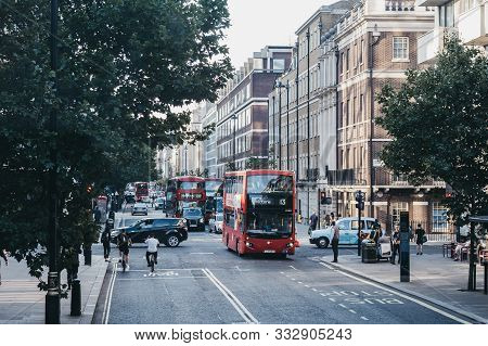London, Uk - July 18, 2019: Cyclists, Red Double Decker Buses And Taxis On A Street In London, Uk, O