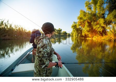 Amateur anglers fishing on the river on sunrise