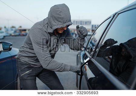 Car thief breaking door lock, criminal job