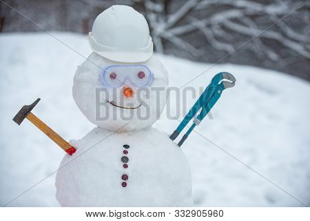 Snowman Worker On Snow Background. Funny Snowman In Work Helmet On Snowy Field. Handmade Snowman In