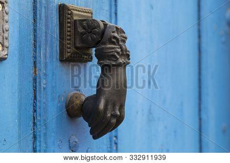 Old Iron Door Handle In The Form Of A Female Hand On Blue Door. Ancient Metal Door Knocker Close-up.