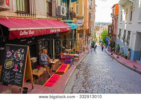 Istanbul, Turkey - September 6th 2019. A Tourist Enjoys  Coffee At A Cafe In A Small Road In The Kab