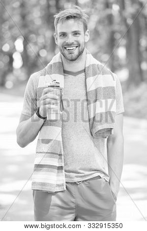 Thirsty after morning jog. Athlete hold bottle care hydration body. Refreshing vitamin drink after great workout. Man athletic appearance holds water bottle. Athlete drink water. Water balance. poster