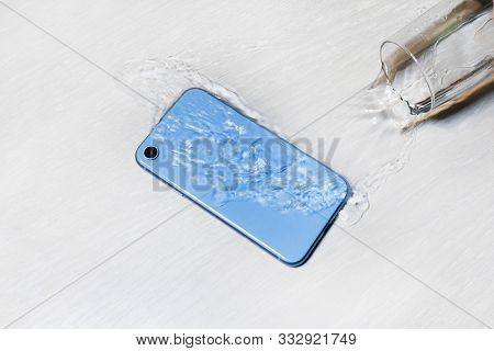 Wet Blue Smartphone In Water On Table, Floor. Accident With Cell Mobile Phone, Water Flowing From Sp