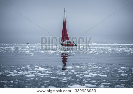 A Small Boat Among Icebergs. Sailboat Cruising Among Floating Icebergs In Disko Bay Glacier During M