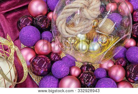 Purple, Pink And Golden Christmas Balls On A Claret Velvet Background.