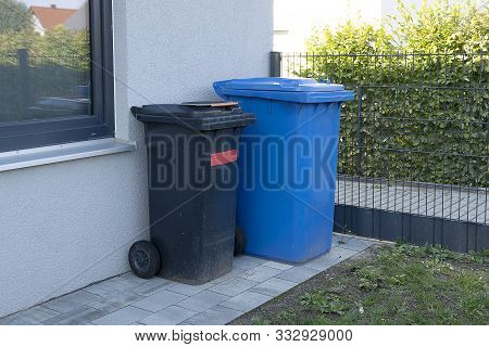 Trash Cans Of Black And Blue On Wheels Stand Near The Wall. Dirty Plastic Mobile Garbage Bins And Ho