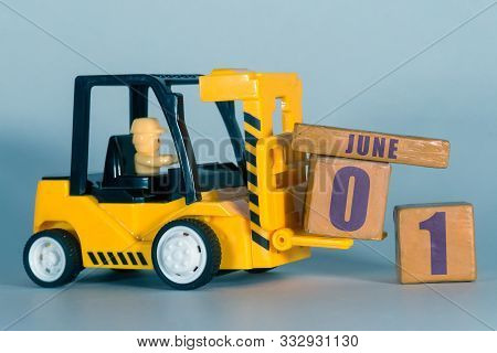 June 1st. Day 1 Of Month, Construction Or Warehouse Calendar. Yellow Toy Forklift Load Wood Cubes Wi