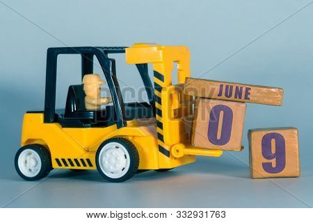 June 9th. Day 9 Of Month, Construction Or Warehouse Calendar. Yellow Toy Forklift Load Wood Cubes Wi