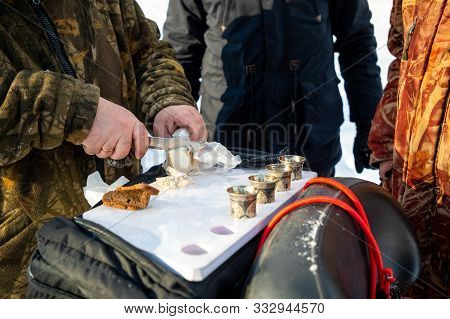 Kemerovo, Russia - 23.02.2019: Man Cuts Lard To Drink Vodka On Nature During Winter Fishing In Siber