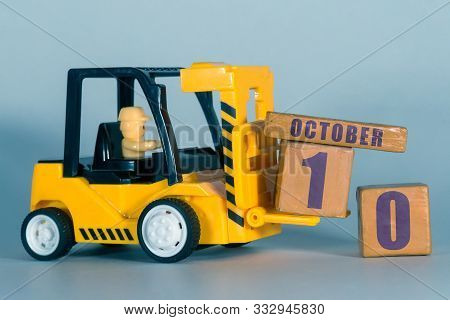 October 10th. Day 10 Of Month, Construction Or Warehouse Calendar. Yellow Toy Forklift Load Wood Cub