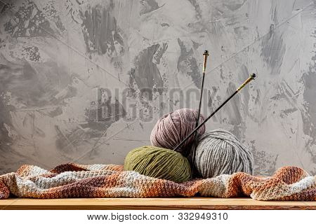 Skeins Of Yarn For Knitting From Natural Wool On A Wooden Surface Or Table. Background - Concrete Wa