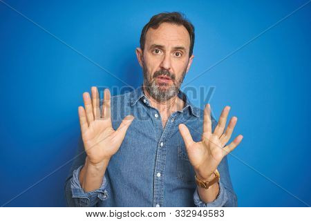 Handsome middle age senior man with grey hair over isolated blue background Moving away hands palms showing refusal and denial with afraid and disgusting expression. Stop and forbidden.