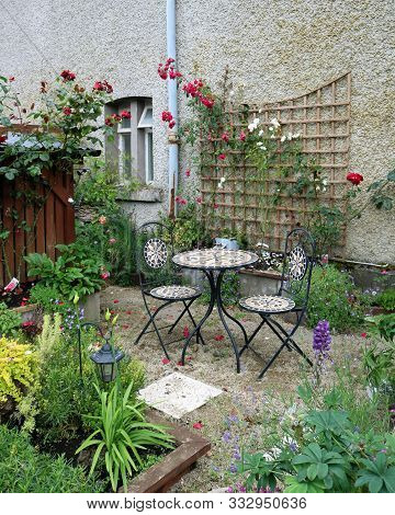 Patio Flowers And Patio Table. Backyard Patio Area With Garden Furniture And Flowers.