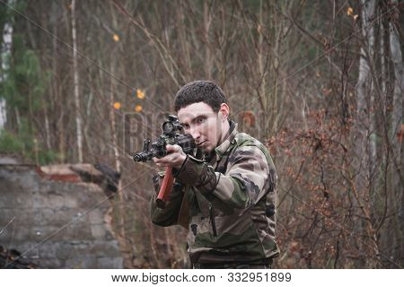 Russian Soldier With Aka-47 Kalashnikov Assault Rifle In Camouflage Aiming At A Target In The Autumn