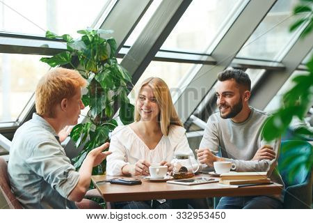 Group of happy young contemporary students gathered by table in cafe after classes for chat and cup of coffee or tea