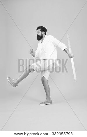 Knowledge In Brutal World. Brutal Hipster Walking With Ruler On Yellow Background. Bearded Man With