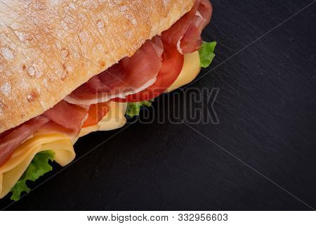 Ciabatta Sandwich With Lettuce , Prosciutto And  Cheese Over Stone Background. Top View With Copy Sp