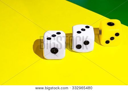 White And Yellow Dice On A Combined Green And Yellow Background