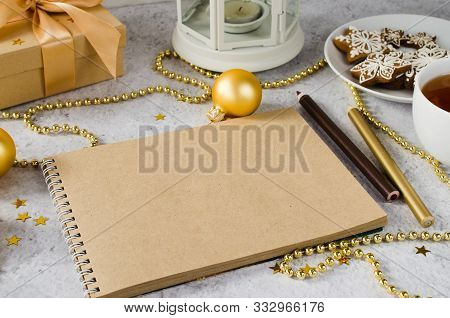 Flat Lay Of Blank Brown Notebook With Gift Box, Tea, Gingerbread Cookies And Lamp. Christmas Mock Up