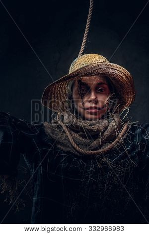 Portrait Of Young Woman On Masquerade In Dreadful Scarecrow Costume On The Dark Background.